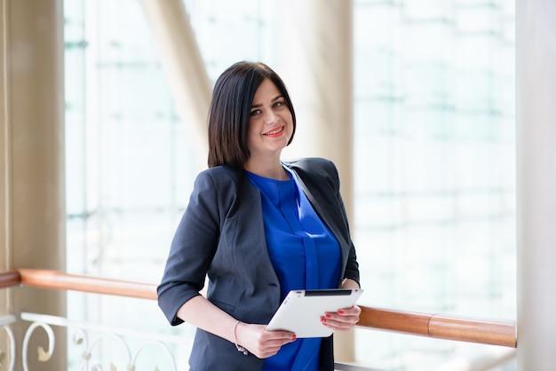 Donna di affari che lavora con un computer portatile e un tablet.