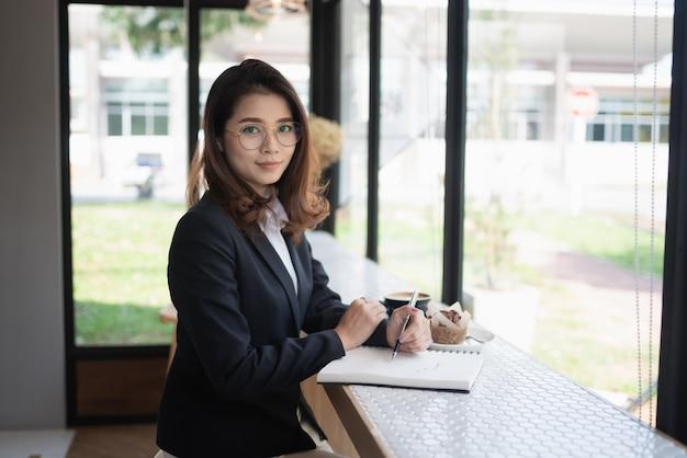 Donna di affari che lavora con il taccuino sul tavolo, concetto di affari