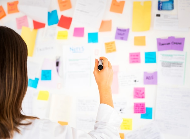 Donna di affari che lavora con le note in un ufficio Foto Premium