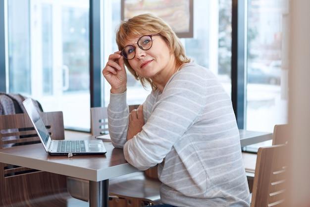 Donna d'affari sul posto di lavoro in ufficio. una donna di mezza età che lavora al computer portatile in un bar. lei sorride.