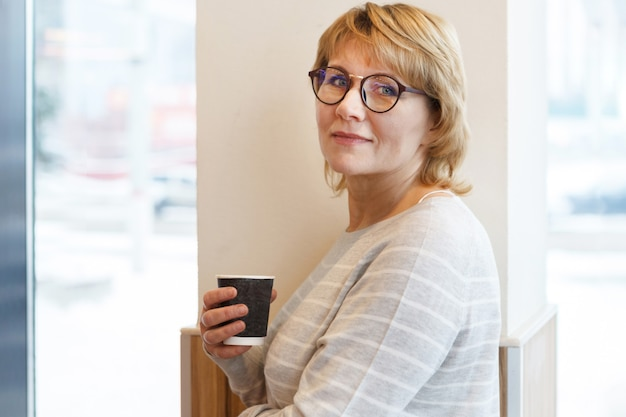 Donna d'affari sul posto di lavoro alla finestra in ufficio. una donna di mezza età tiene un bicchiere di caffè in un bar. lei sorride.