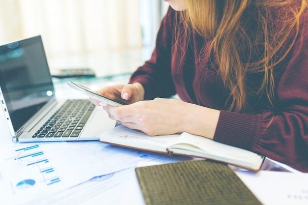 La donna d'affari lavora a casa, il lavoro a distanza a casa, con il laptop e con il notebook, prende appunti al telefono