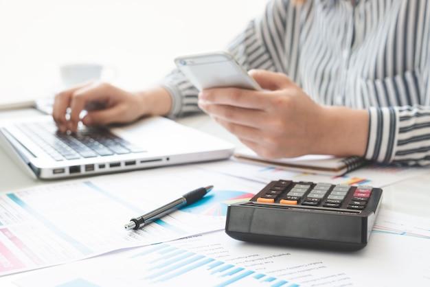 La scrittura della donna di affari prende nota con calcola. tasse e concetti economici. risparmio, finanze.