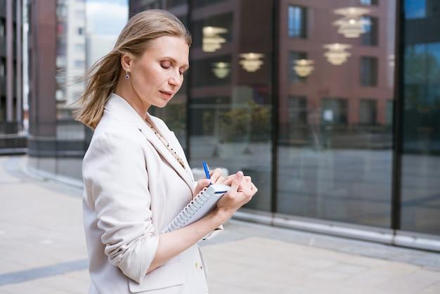 Donna d'affari che scrive con la penna nel taccuino ragazza caucasica di successo in giacca leggera si trova vicino a un...
