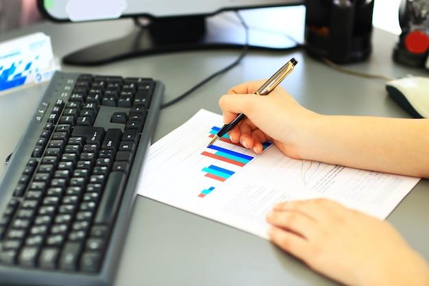 Donna d'affari che scrive con la penna in ufficio