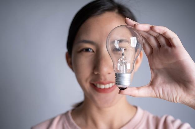 Mano delle donne d'affari che tiene la lampadina, concetto di nuove idee con innovazione e creatività