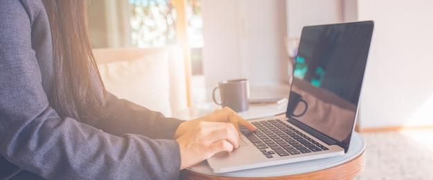 Computer portatile di uso della mano delle donne di affari.