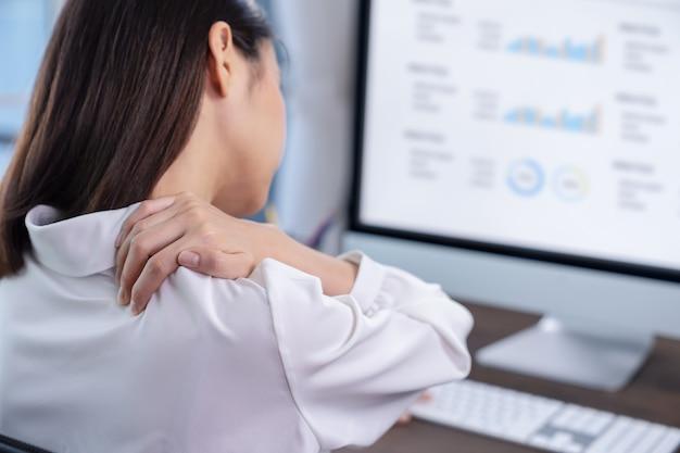 Le donne d'affari hanno dolori alla spalla lavorando a lungo sullo schermo di un computer. potrebbe essere la sindrome dell'ufficio.