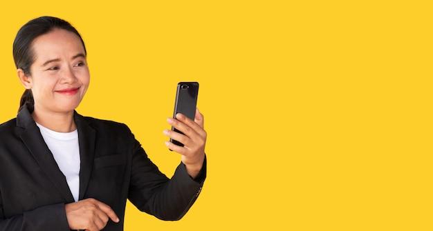 Le donne d'affari usano gli smartphone per effettuare videochiamate su uno sfondo giallo