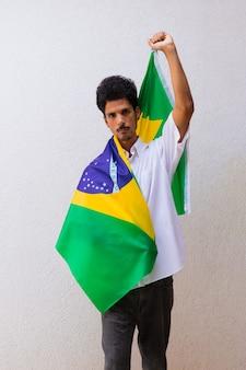 Azienda o lavoratore in possesso di una bandiera del brasile isolata su bianco. bandiera e immagine del concetto di festa dell'indipendenza.