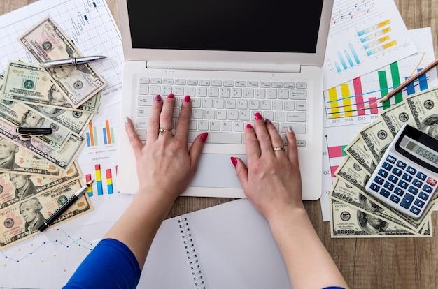 Il lavoratore di affari sta tenendo i dollari degli stati uniti in mano con il computer portatile e il grafico commerciale