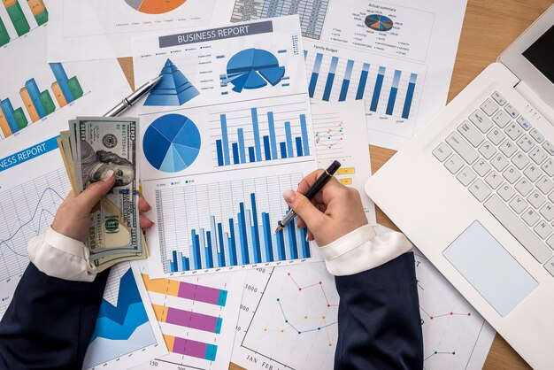 Lavoratore di affari sta tenendo in mano dollari usa con laptop e grafico commerciale