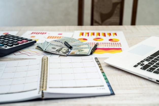Computer portatile dei soldi del posto di lavoro di affari e grafico di affari all'ufficio risparmia e denaro concetto
