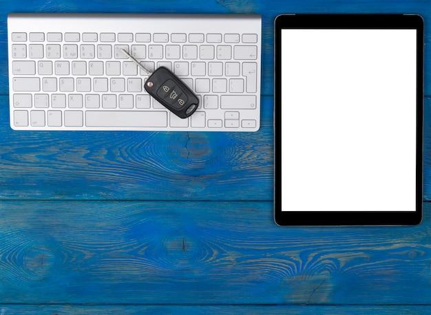 Posto di lavoro aziendale con tastiera wireless, computer tablet e chiavi dell'auto su fondo di legno blu. scrivania da ufficio con copia spazio. spazio vuoto per il testo