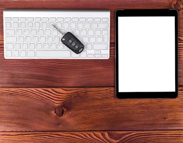 Posto di lavoro aziendale con tastiera wireless, computer tablet e chiavi dell'auto su fondo di legno rosso. scrivania da ufficio con copia spazio. spazio vuoto per il testo