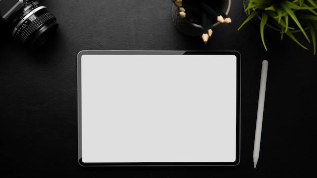 Modello di schermo vuoto della tavoletta digitale dell'area di lavoro aziendale su sfondo nero vista dall'alto piatto lay