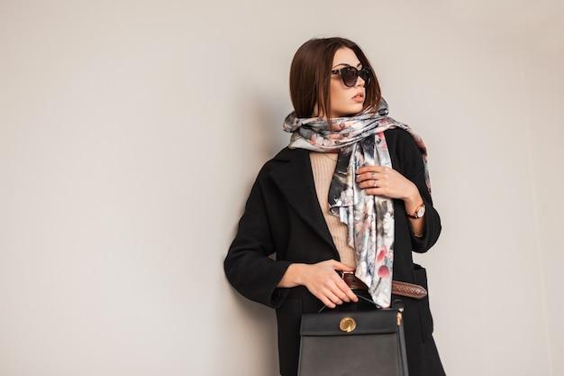 Business giovane donna bruna in eleganti occhiali da sole in un cappotto nero con una borsa in pelle alla moda in un'elegante sciarpa in posa vicino a un muro vintage sulla strada. bella ragazza alla moda. signora di bellezza.