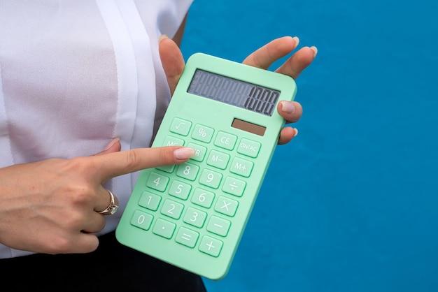 Giovane signora di affari con la calcolatrice verde isolata su fondo blu. concetto di finanza
