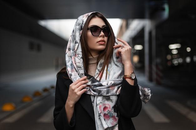 La giovane donna abbastanza bella di affari in occhiali da sole scuri alla moda in un cappotto nero in sciarpa di seta chic sulla testa sta sulla strada. modello di moda bella ragazza in posa in strada. bella signora sexy.