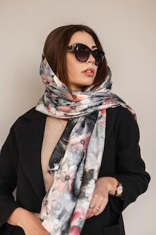 Business giovane donna abbastanza bella in eleganti occhiali da sole scuri in un cappotto nero in elegante sciarpa di seta sulla testa si trova in strada. modello di moda della bella ragazza che posa vicino alla parete. bella signora sexy.