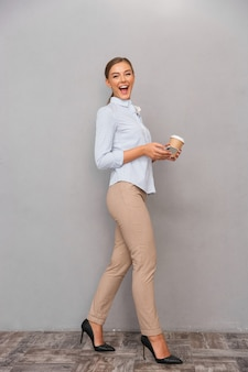 Giovane donna di affari che posa isolata sopra il fondo grigio della parete facendo uso del caffè bevente del telefono cellulare.