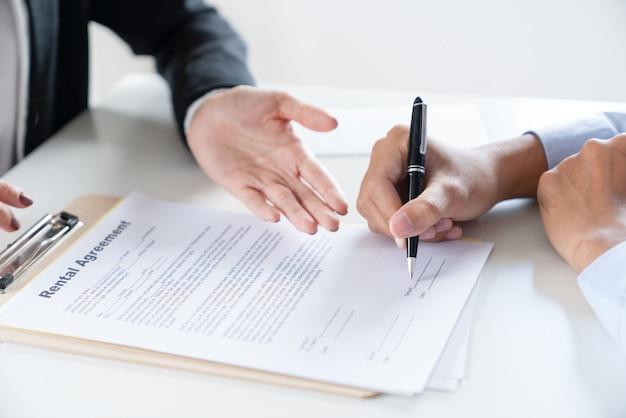 Documento di contratto di acquisto del contratto di mutuo per la casa del segno della mano di businessan con l'agente immobiliare della proprietà