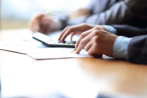 Mano dell'uomo d'affari o contabile che tiene la matita che lavora sulla calcolatrice per calcolare i dati finanziari