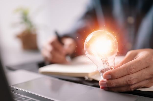 Ragioniere dell'uomo d'affari che tiene lampadina, nuova idea con il concetto dell'innovazione