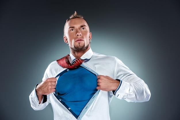 Uomo d'affari che si comporta come un super eroe e si strappa la maglietta su uno sfondo grigio