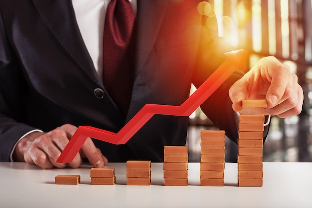L'uomo d'affari aggiunge un mattone per far crescere la tendenza finanziaria. la freccia rossa mostra la crescita. concetto di successo, statistica e profitto