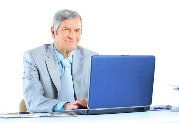 L'uomo d'affari all'età dei lavori per il laptop. isolato su uno sfondo bianco.