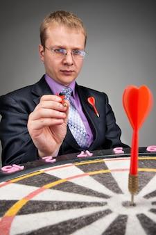 Uomo d'affari che mira a prendere di mira il dardo rosso