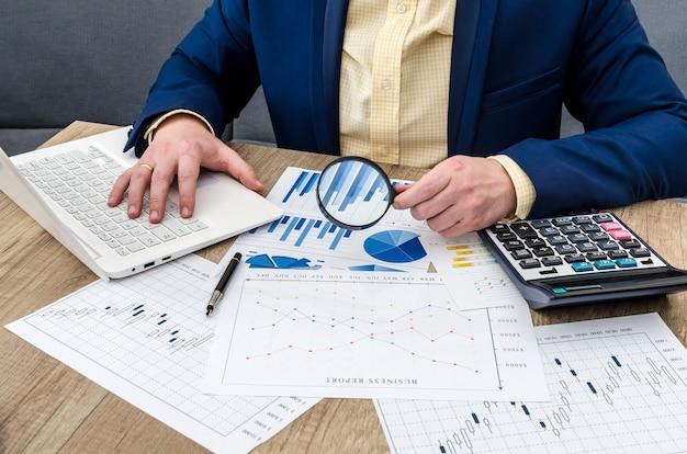 Uomo d'affari che analizza i grafici di affari con la lente d'ingrandimento