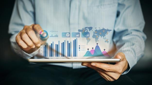 Uomo d'affari che analizza società finanziaria lavorando con i grafici digitali di realtà aumentata.