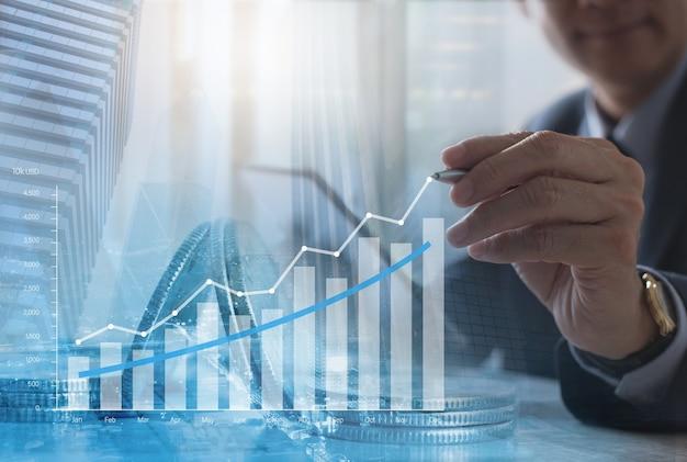 Uomo d'affari che analizza il rapporto finanziario con il grafico economico sullo schermo virtuale
