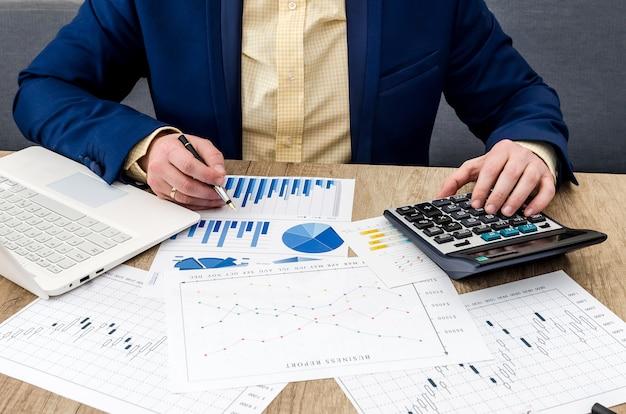 Uomo d'affari che analizza grafici e diagrammi su un tavolo di legno