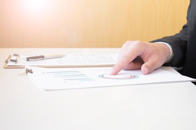 Uomo d'affari che analizza grafici e numeri di investimento. contabilità