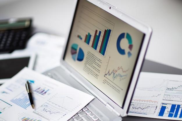 Uomo d'affari analizzando i grafici di investimento con il computer portatile. contabilità