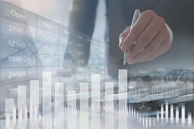 Uomo d'affari che analizza i dati di vendita con il grafico finanziario sullo schermo virtuale