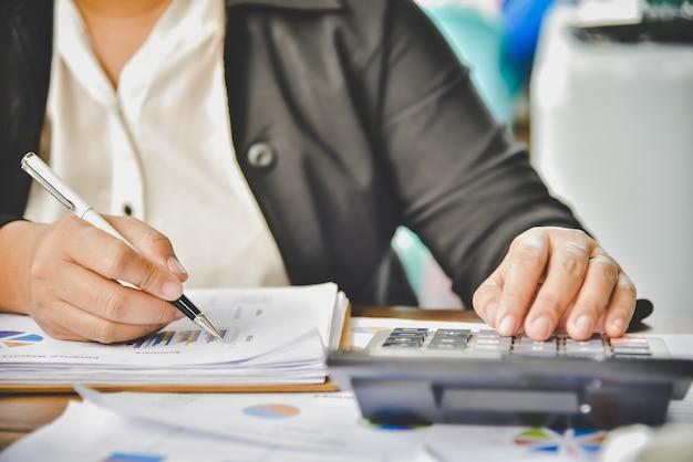 L'uomo d'affari sta lavorando con una calcolatrice e un documento. relazione della riunione in corso. nel concetto di affari di ufficio