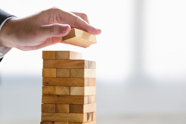 Uomo d'affari che sistema a mano blocco di legno e che impila come torre.