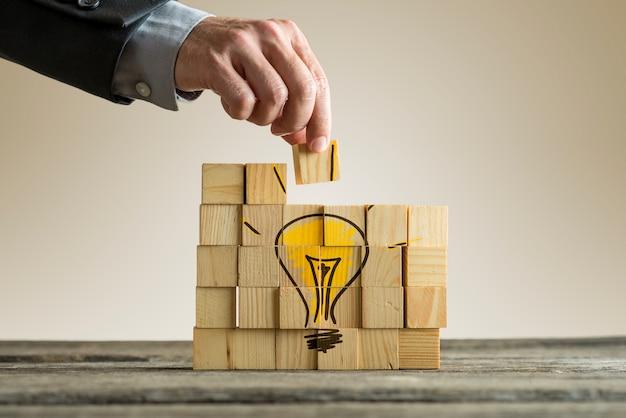 Uomo d'affari che organizza i blocchi di legno che formano una lampadina gialla