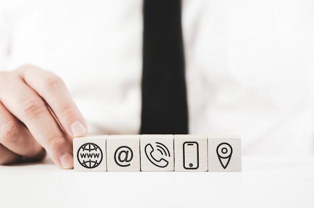 Uomo d'affari che monta i blocchi bianchi con le icone del contatto stampate su loro