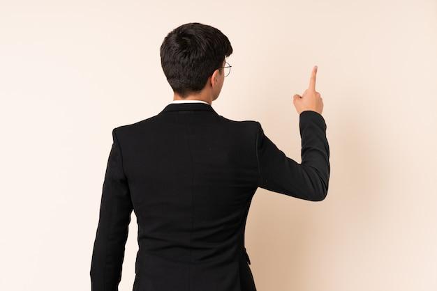 Uomo d'affari sopra la parete beige che indica indietro con il dito indice
