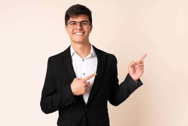 Uomo d'affari sopra la parete beige che indica dito il lato