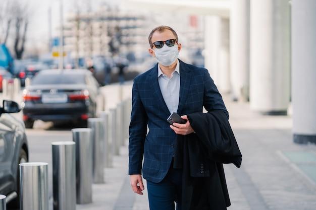 Uomo d'affari in abiti eleganti neri, maschera medica, tiene in mano lo smartphone, cammina attraverso la città frenetica con molti mezzi di trasporto, si protegge dal coronavirus durante la pandemia.