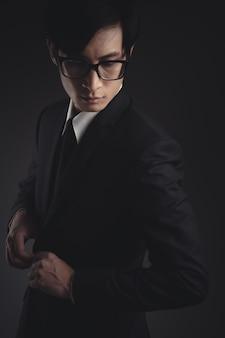 Uomo d'affari in abito nero su fondo nero