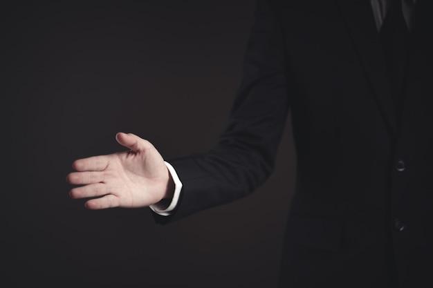 Uomo d'affari in abito nero mano aperta pronta a trattare e si stringono la mano sul nero