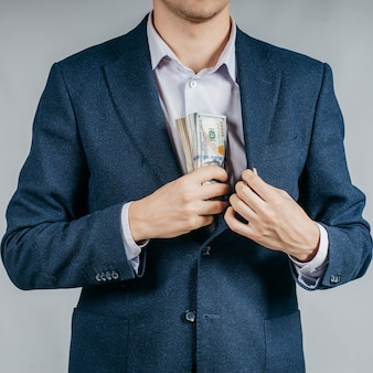 Uomo d'affari in un vestito nero che mette soldi in tasca