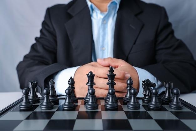 Uomo d'affari in vestito nero che si siede e squadra di controllo davanti alla posizione di successo sul gioco di scacchi di affari della concorrenza.
